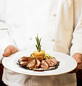 A Chef Holding Sliced Duck Breast Entrée
