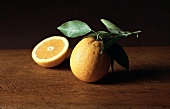 A Whole and Halved Orange with Leaves on Wood
