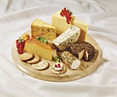 Cheese and crackers on a wooden board with red currants