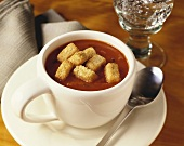 A cup of tomato basil soup with croutons