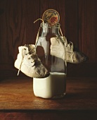 Glass bottle of milk with baby booties