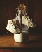 Eine Flasche Milch mit Babyschuhen