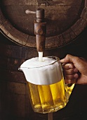 Pouring a pitcher of beer from a wooden keg