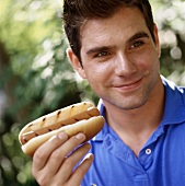 Young man with grilled hot dog in the open air