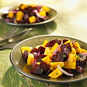 Red and Golden Beet Salad with Red Onion Served on Green Plates