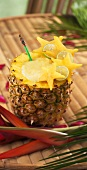 Tiki Pineapple Drink Served in Pineapple on Bamboo Table; Tropical Flowers