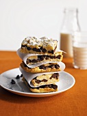 A Stack of Chocolate Chip Cookie Bars with Powdered Sugar and Milk