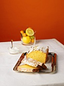 A Loaf of Lemon Cake, Partially Sliced, on a Silver Tray