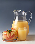 Pitcher and Glass of Grapefruit Juice with Bowl of White and Pink Grapefruit Slices