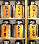 Several Chinese tea caddies on shelves