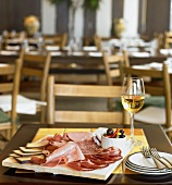 Platter of Assorted Meats with Cheese, Olives and Glass of White Wine