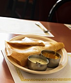 Serving of Indian Dosa with Two Assorted Sauces; In a Restaurant