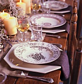 Holiday Table Setting with Black and White Plates, Candles and Glasses