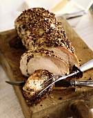 Partially Sliced Herb Crusted Pork Loin on Cutting Board with Serving Utensils
