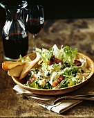 Bowl of Mixed Baby Greens Salad with Blue Cheese and Bacon and Bread; Red Wine