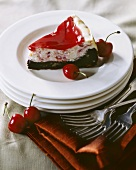 Slice of Cherry Cheesecake with a Brownie Crust and Cherry Topping on White Plate; Cherries