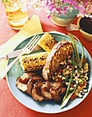 Serving of Sliced Pork with Barbecue Sauce, Grilled Corn on the Cob, Grilled Bread and Bean Salad