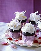 Mini Chocolate Cupcakes with White Icing and Toasted Coconut Shavings; Rose Petals