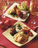 Assorted Christmas Appetizers on Square Plates; Glasses of White Wine and Christmas Decorations