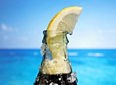 Ice Cold Bottle of Cola with Lemon Wedge, Close Up, by the Ocean
