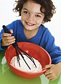 Boy whipping cream with whisk