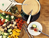 Cheese Fondue in Fondue Pot with Assorted Bread Cubes and Vegetables For Dipping