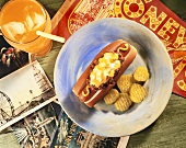Overhead of Chili Cheese Dog with Mustard and Pickle Slices; Glass of Orange Soda