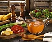 Glass Pitcher of French Dressing with Salad Ingredients Sliced on Cutting Board; Salad Servers