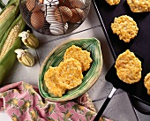 Corn Fritters on a Plate; Spatula Removing Corn Fritters From Skillet; Fresh Corn and Eggs