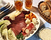 New England Boiled Dinner; Sliced Corned Beef with Cabbage, Potatoes and Carrots on a Platter