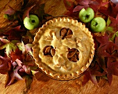 Overhead of Apple Pie with Apple Shaped Cut-Outs from Top Crust; Autumn Leaves and Apples