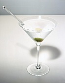 Martini with olive in glass with condensation