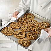 Baker holding baking tray of freshly-baked cookies