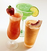 Three frozen cocktails garnished with fruit