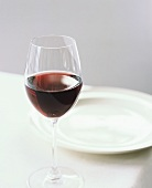 A Glass of Red Wine at a White Table Setting