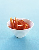 Red Pepper Strips in a White Bowl on a Blue Background