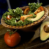 Salad with Tomato and Avocado in a Bowl, Tomato and Half an Avocado
