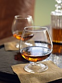 Brandy in a Brandy Snifter on a Napkin; Another Glass of Brandy with Decanter