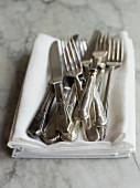 Forks and Knives Piled on a Pile of White Cloth Napkins