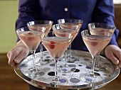 Person holding a silver tray of raspberry Martinis