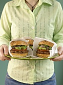 Woman carrying three hamburgers wrapped in napkins