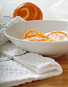 Candied Orange Zest in Bowl of Sugar; Partially Zested Orange