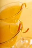 Two Citrus Martinis Garnished with Orange Zest on an Orange Background