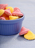 Pink and Yellow Melty Mints In and Beside a Blue Glass Bowl