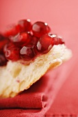 Fresh Pomegranate Seeds on a Slice of Crusty Bread; Red Background