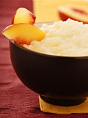Rice Pudding Garnished with Peach Slices Served in a Black Bowl