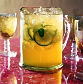 Lime cocktail with ice cubes in a glass jug