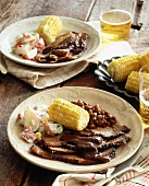 Beef brisket with baked beans, corn on the cob, potato salad