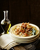 Spaghetti with shrimps and tomatoes, olive oil behind