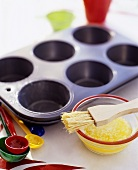 Muffin tin and melted butter with brush
